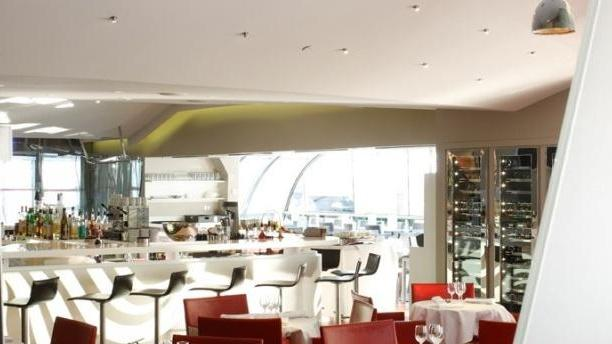 Brasserie Publicisdrugstore Salle tables rondes, nappes blanches, chaises rouges du restaurant  Publicis Drugstore
